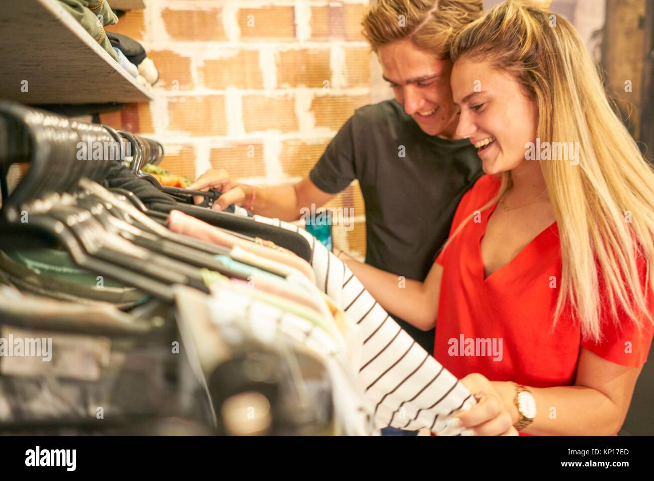 Happy young Dutch couple shopping together clothes in clothing fashion store - Stock Image