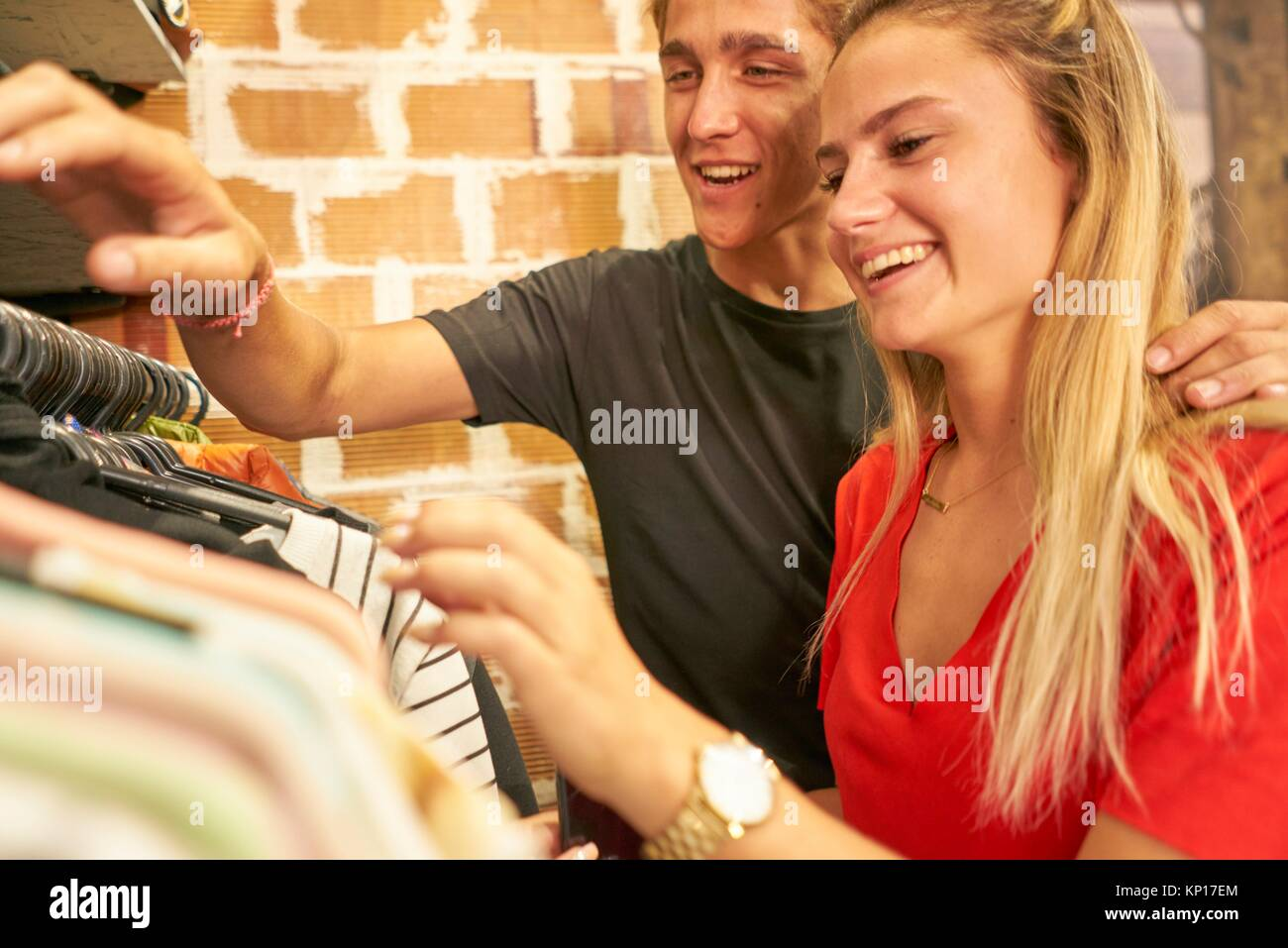 Happy young Dutch couple shopping together clothes in clothing store - Stock Image