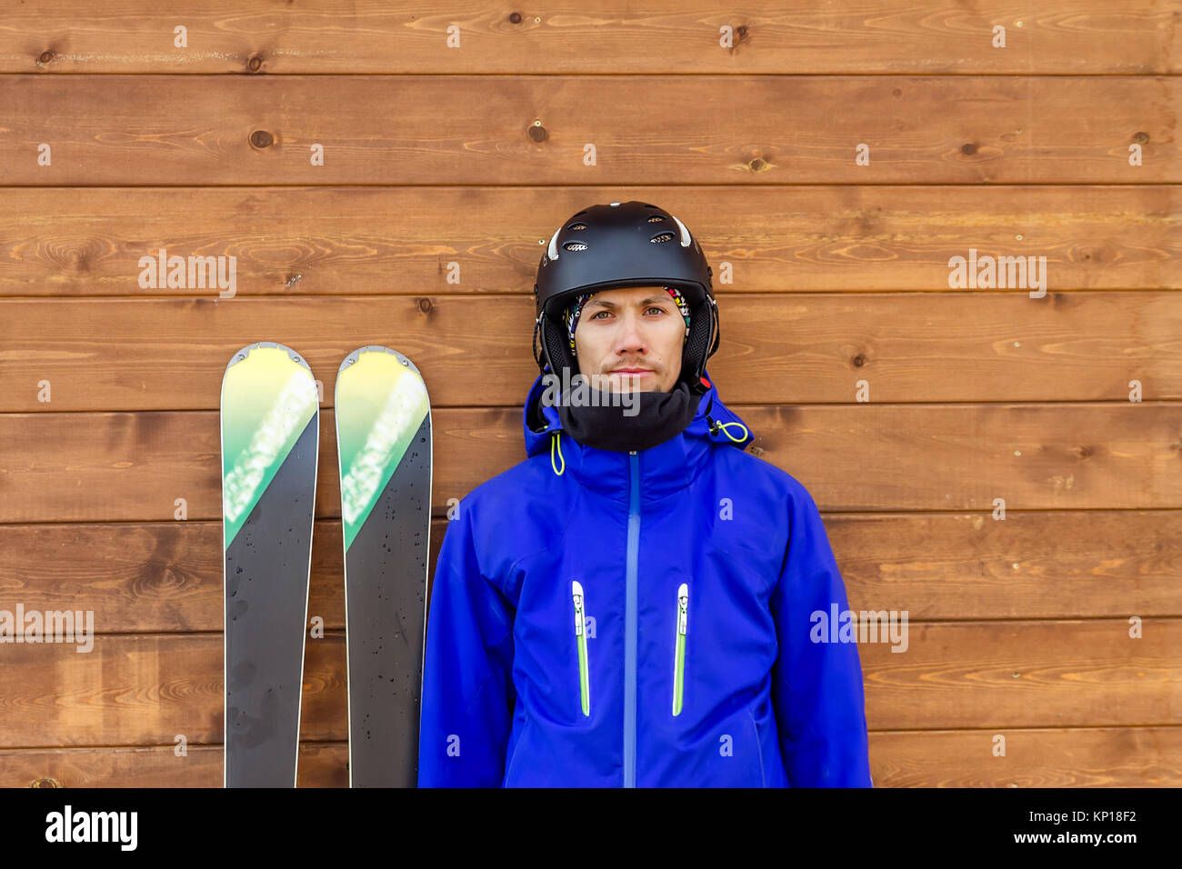 portrait man skier with skis and helmet and ski boots near wooden wall. - Stock Image