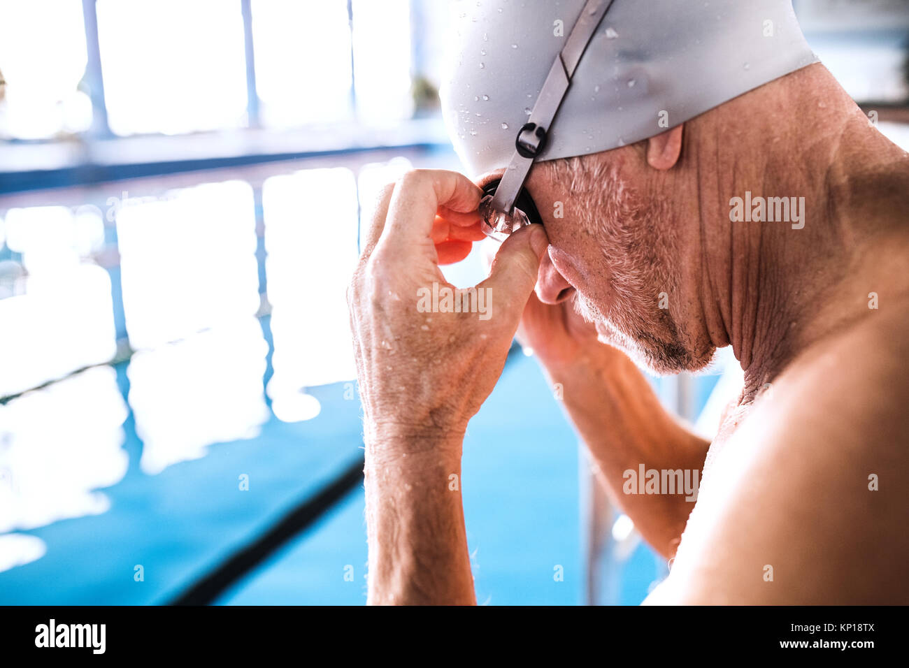 Senior man in an indoor swimming pool. - Stock Image