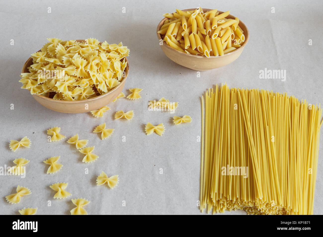 Composition of uncooked italian pasta. Pasta in a pottery. Spaghetti, farfalle, fusilli on gray background. Raw Stock Photo