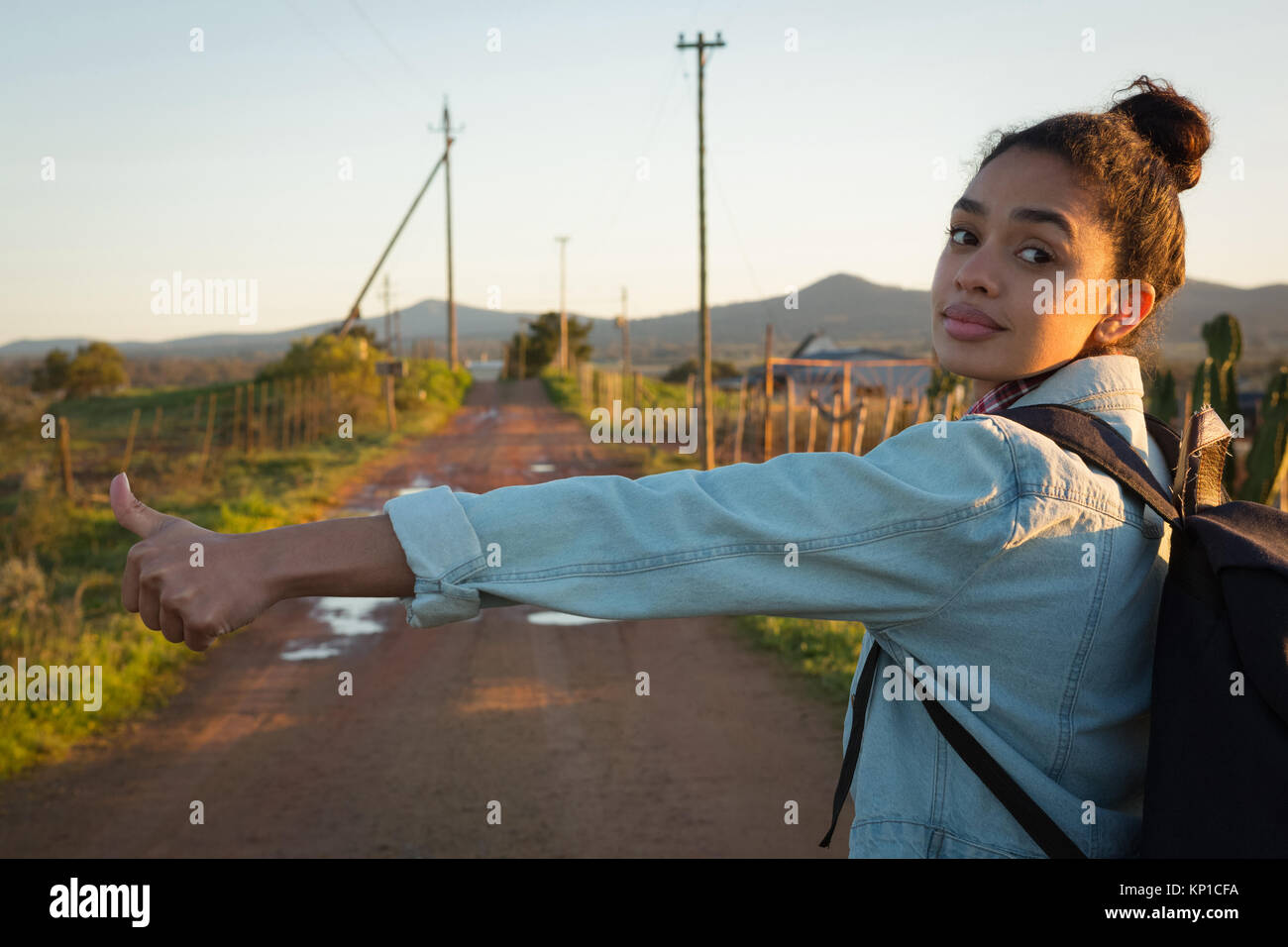 Young woman hitchhiking on a sunny day Stock Photo
