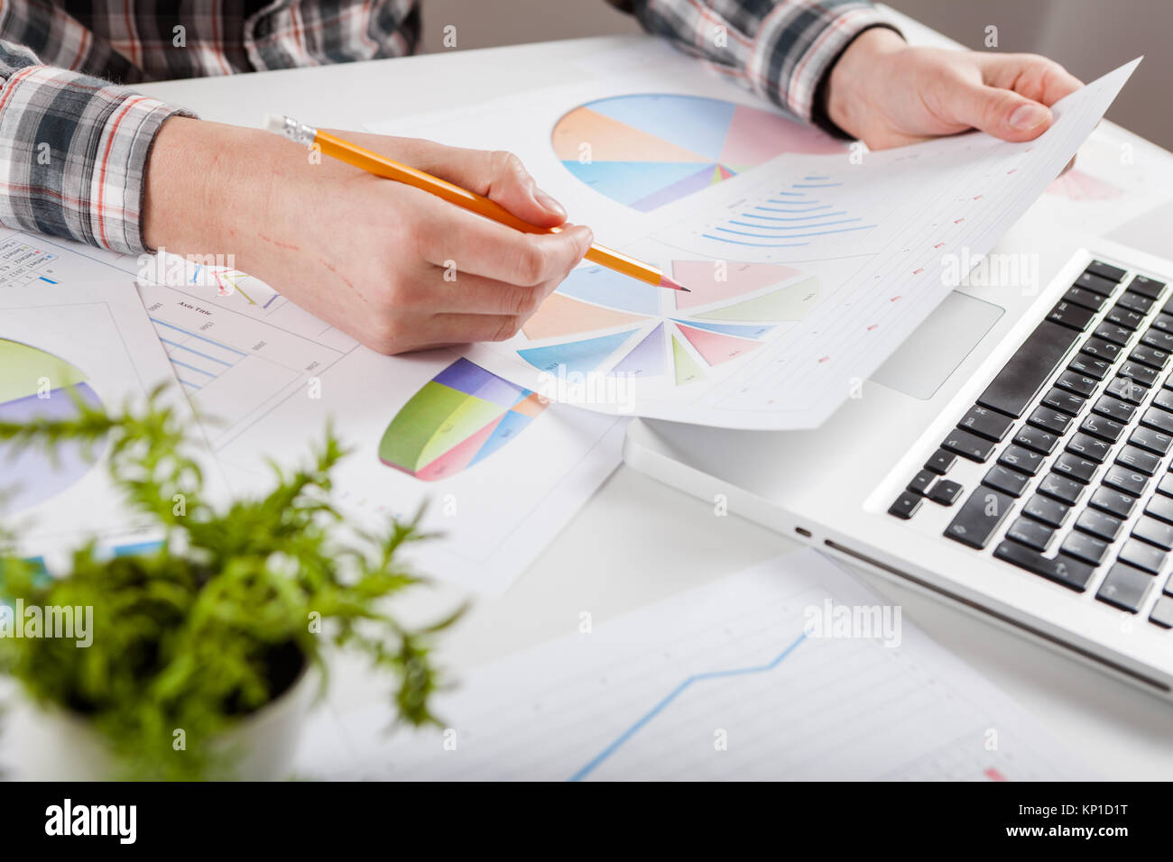 Businessman holding a pen is working with graph documents. Stock market chart and finger pointing on tablet in office. - Stock Image