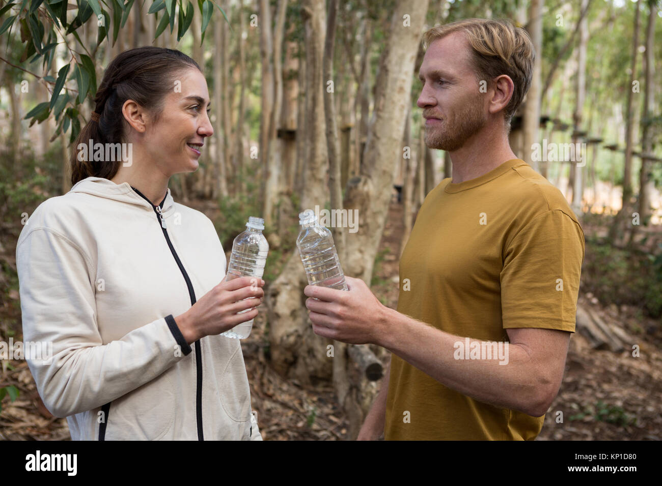 Smiling couple looking at each other holding water bottle in there hands in the forest - Stock Image
