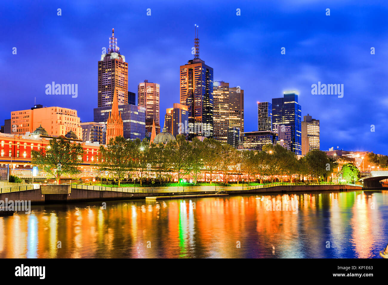 BLue darkness over Melbourne city CBD towers above Flinders train station with bright illumination reflecting in - Stock Image
