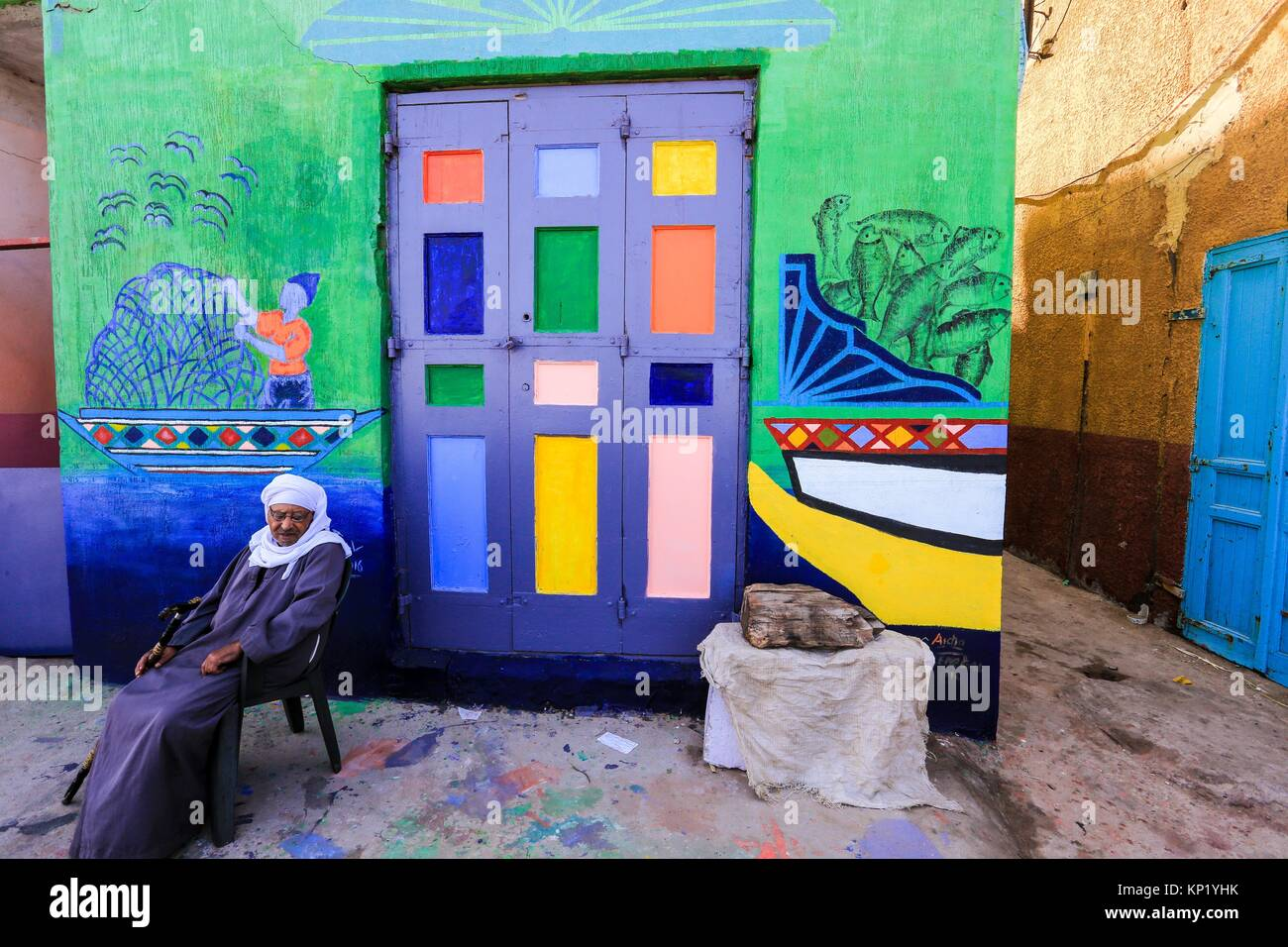 Old man siting in front Painting Walls and Boats, Kafr El-Sheikh governorate, Egypt - Stock Image