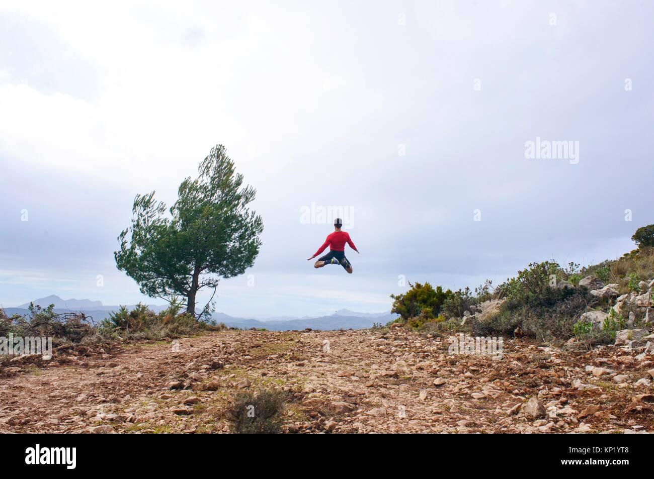 Sportsman jumping through the air in the mountains of Quatretondeta, Alicante, Valencia, Spain Stock Photo