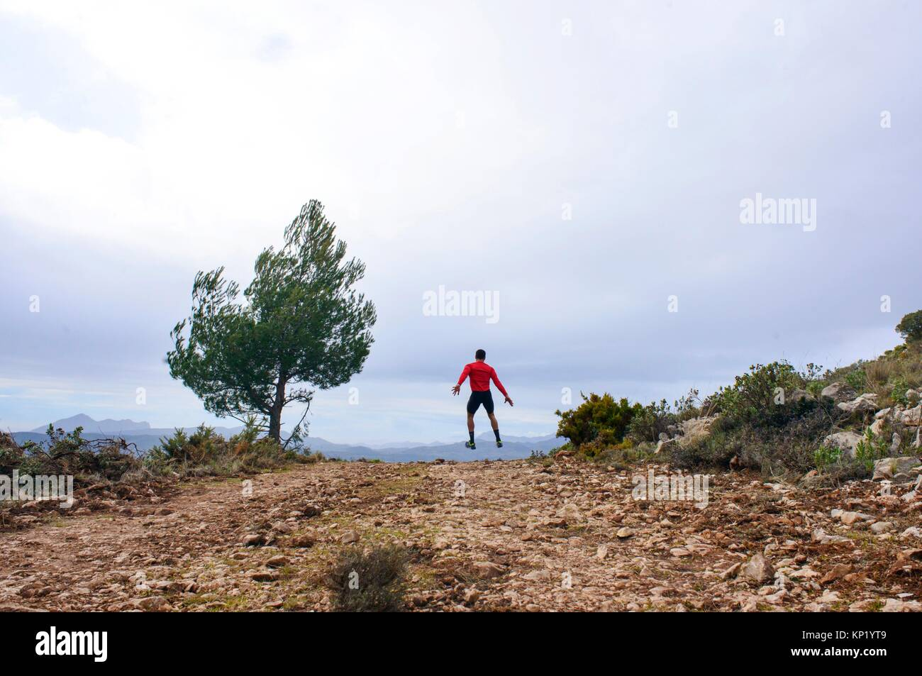 Sportsman jumping through the air in the mountains of Quatretondeta, Alicante, Valencia, Spain - Stock Image