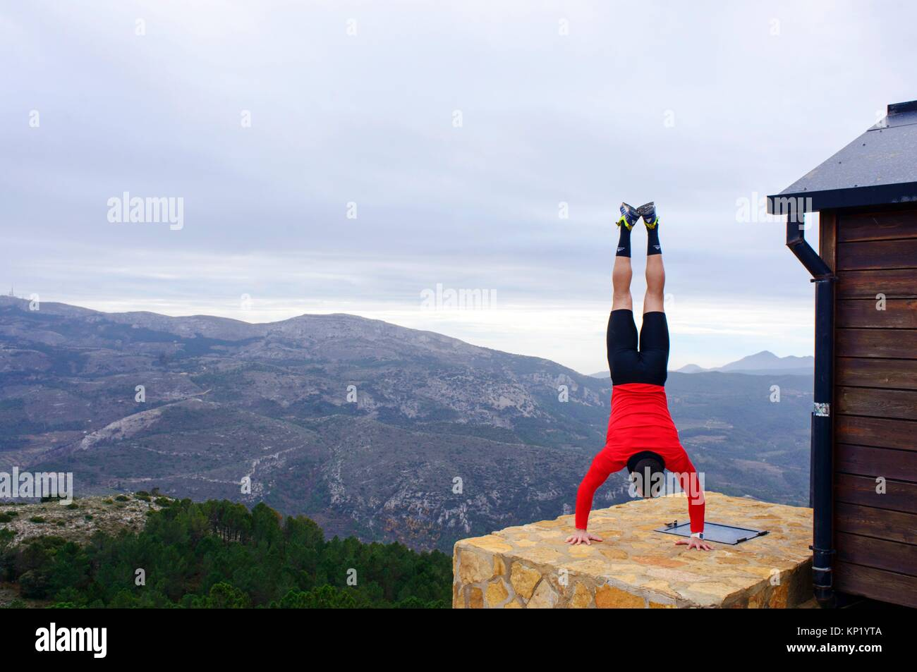 Sportswoman doing handstands in the mountains of Quatretondeta, Alicante, Valencia, Spain - Stock Image