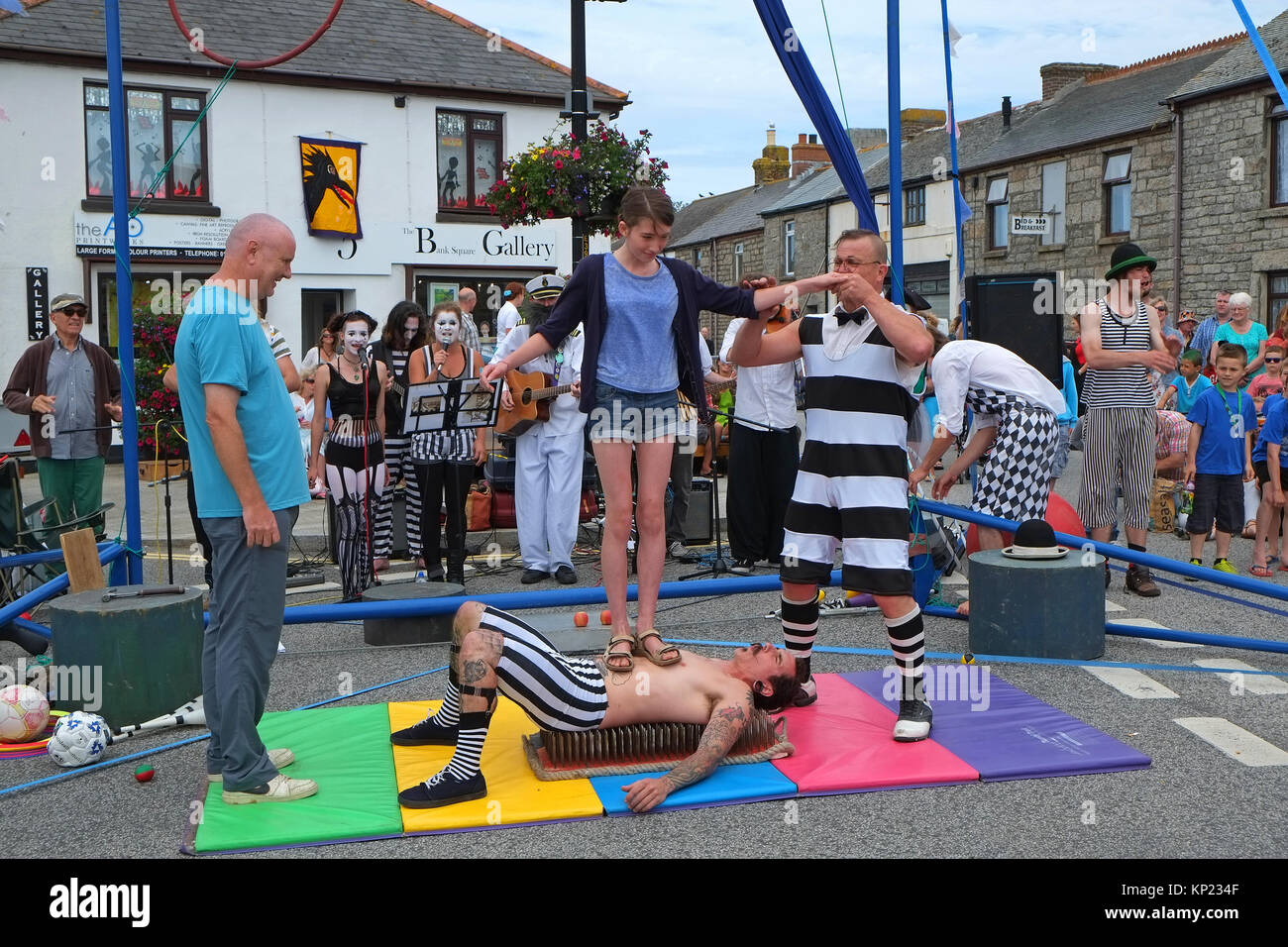 """performance of the """" bed of nails """" trick at the lafrowda festival in st.just, cornwall, england, uk. - Stock Image"""
