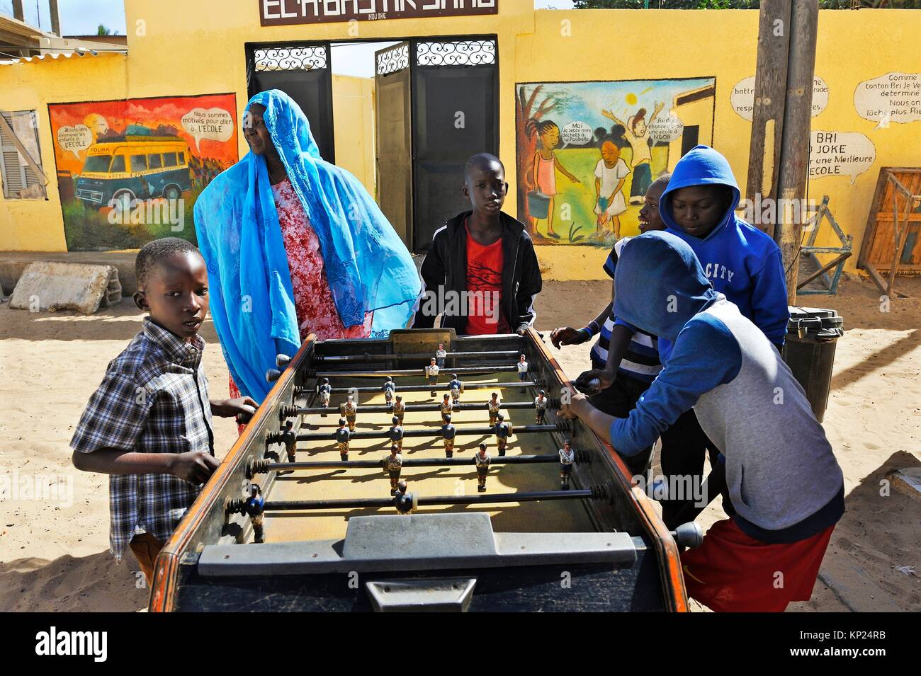 children playing table football in front of the school in the village of Ngor, Almadies headland, Dakar, Senegal, - Stock Image