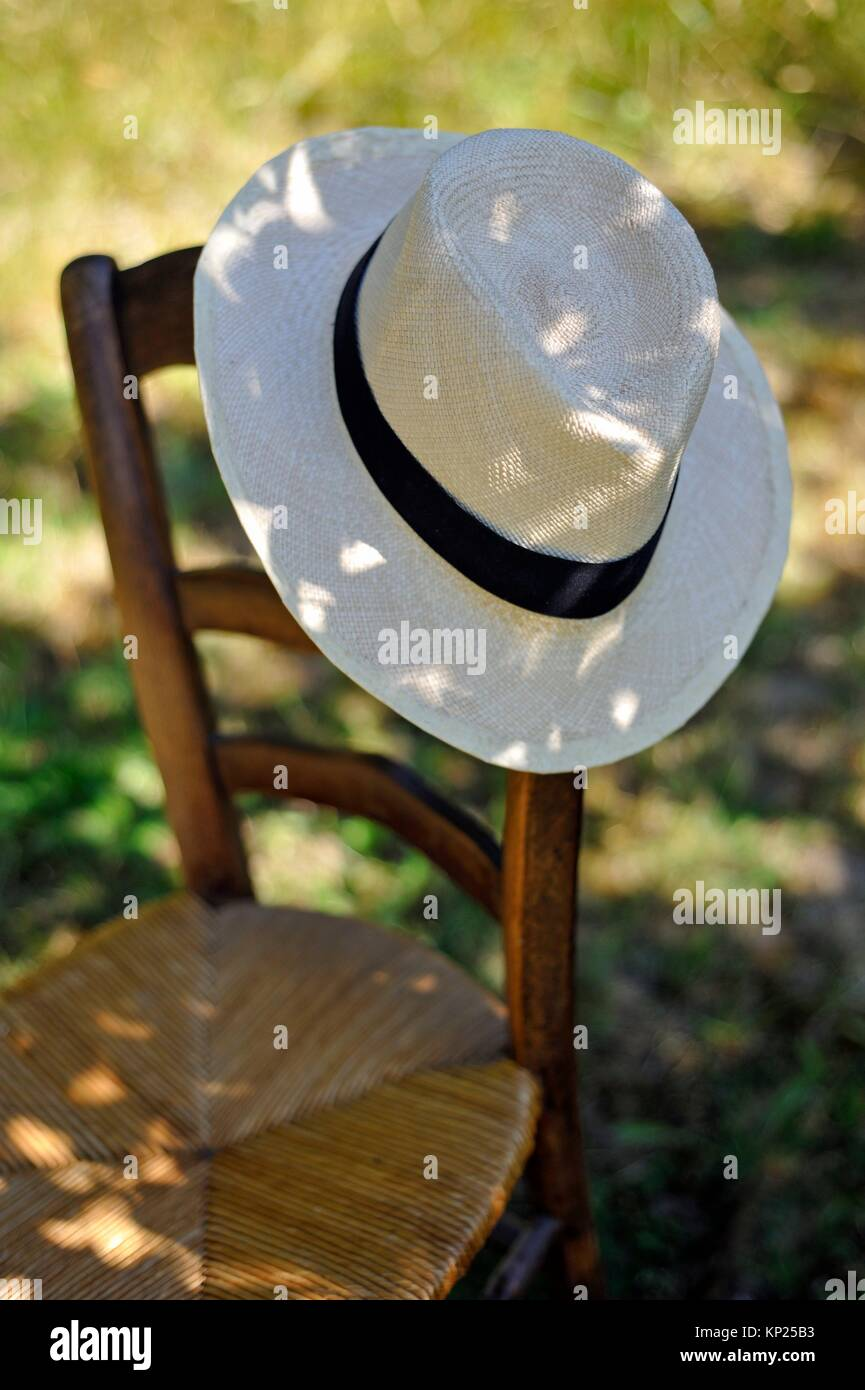 Panama hat placed on a chair back. - Stock Image