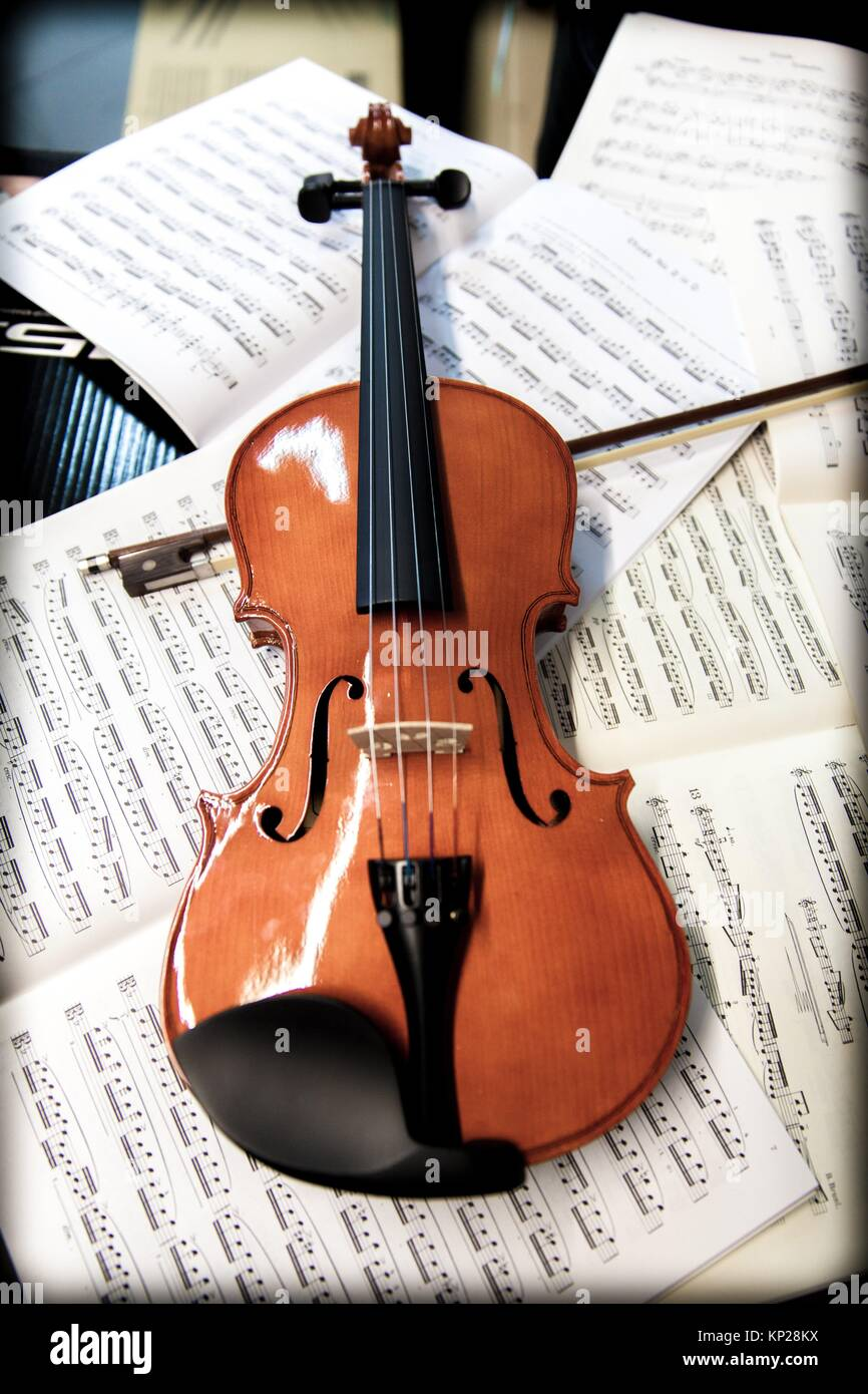 violin laying on sheets of music Stock Photo