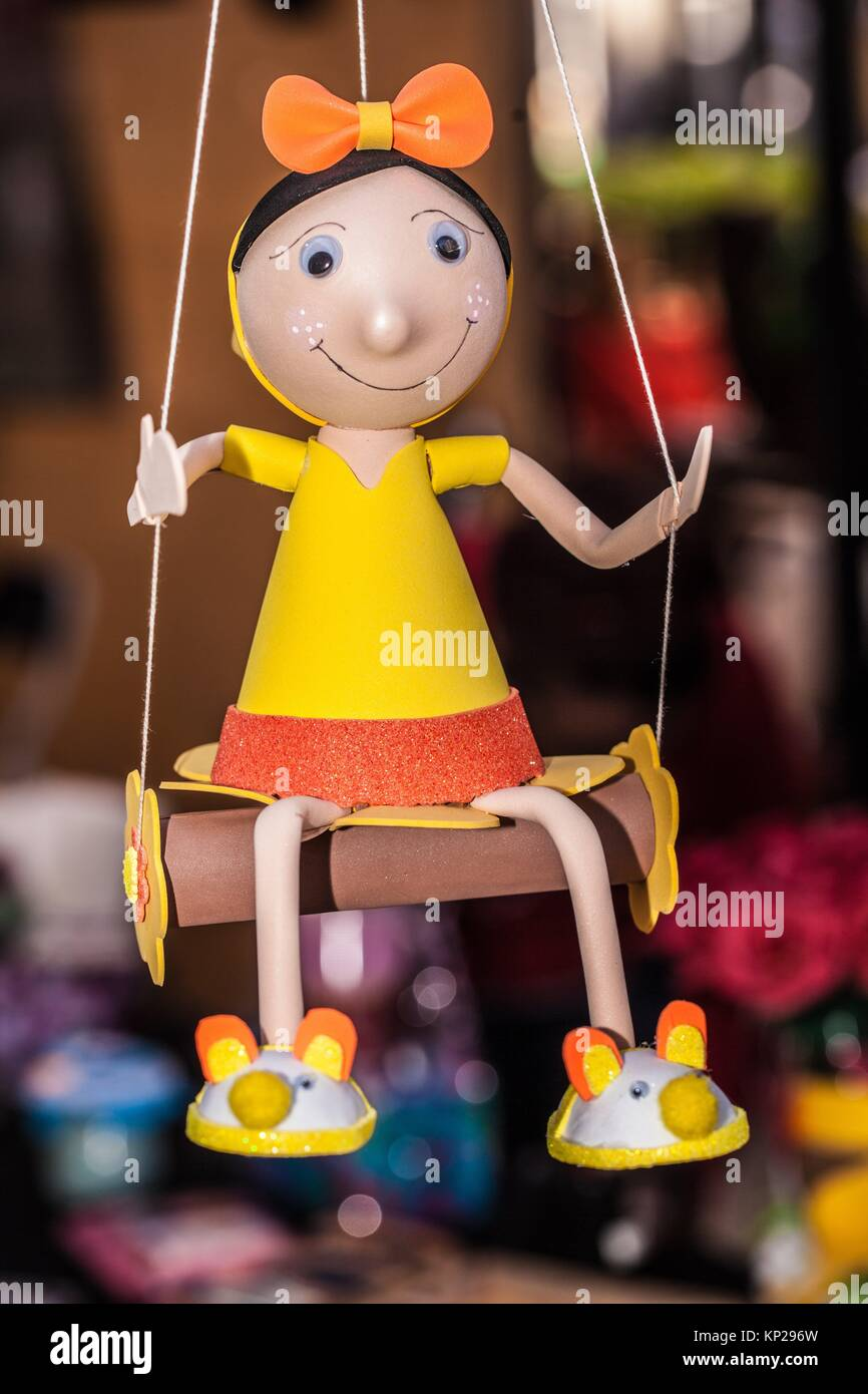 handmade wooden dressed girl doll on a swing - Stock Image