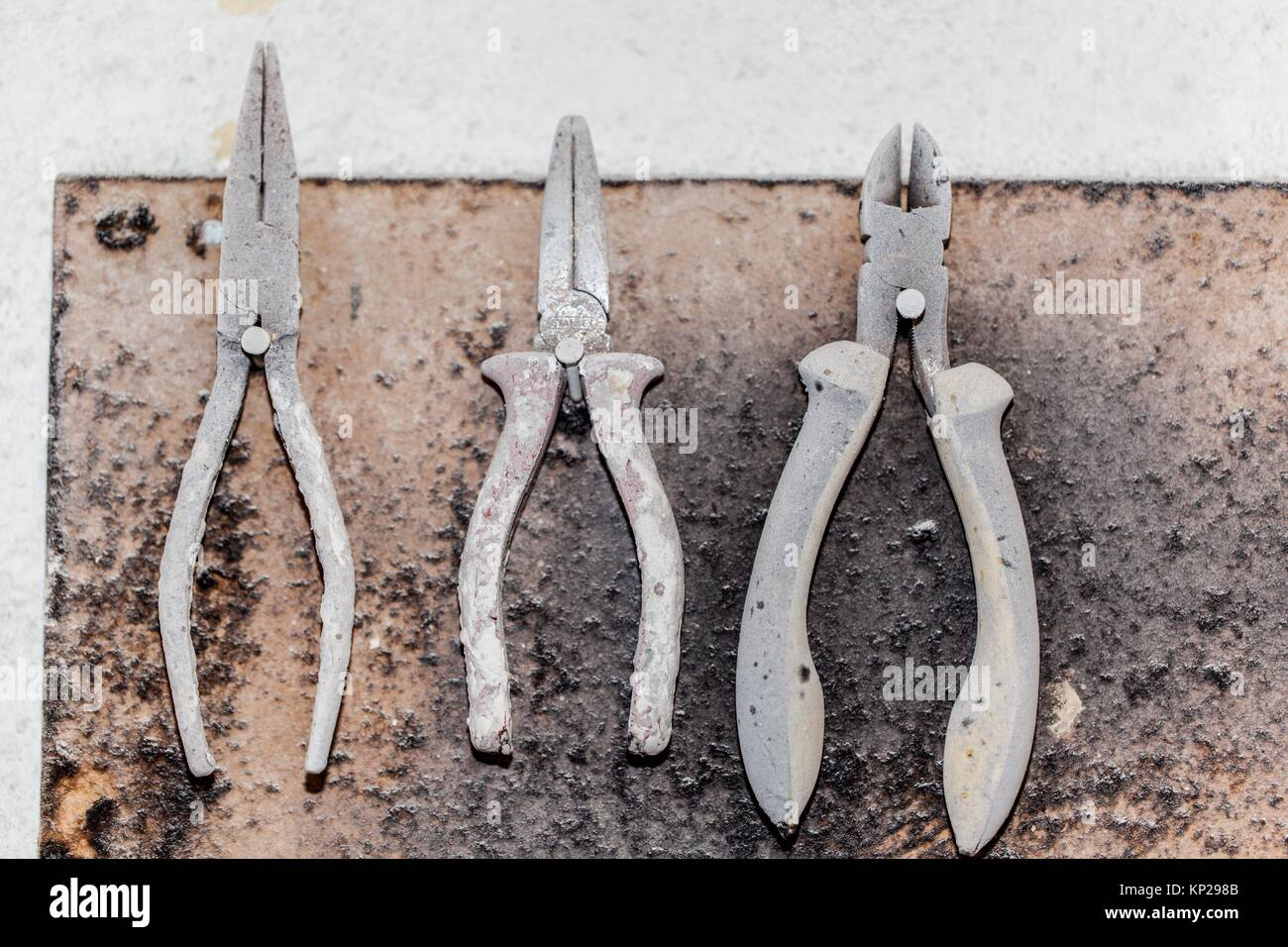 panel of pincers or pliers hanging on a white wall - Stock Image