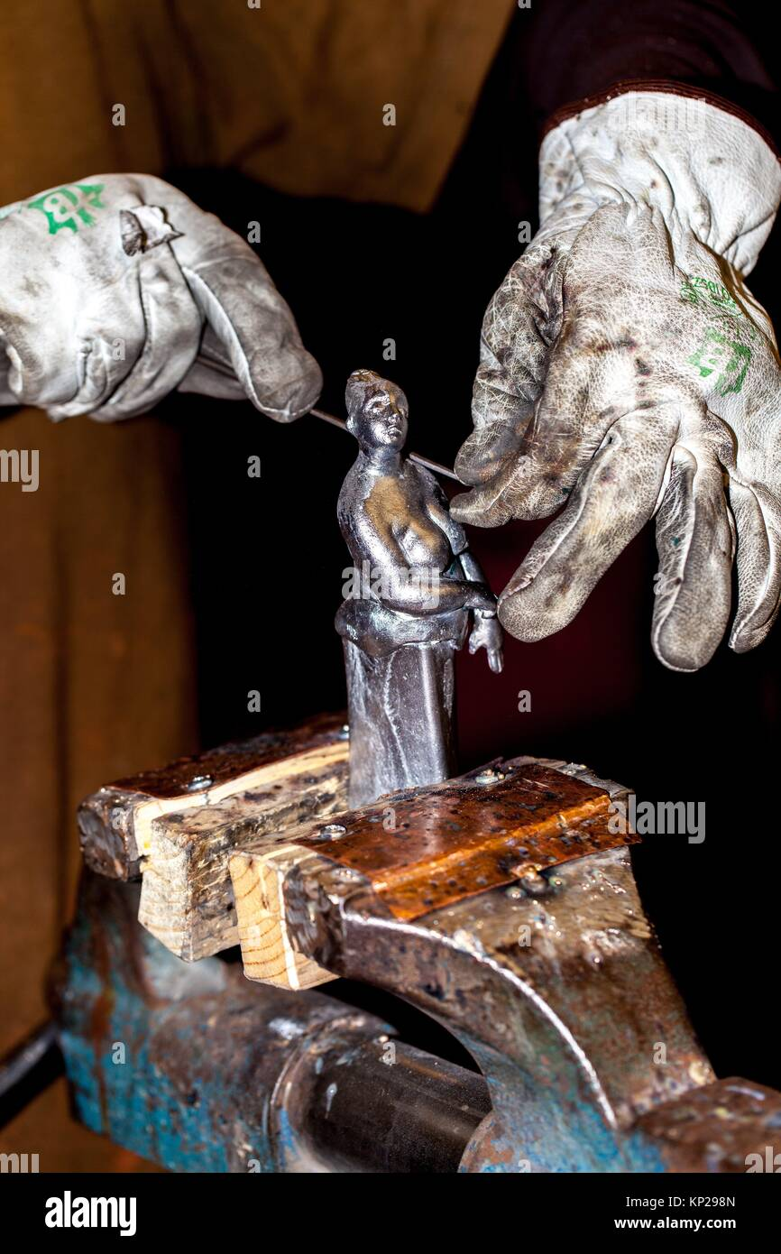 artisan carving a a small metal sculpture on a vice - Stock Image