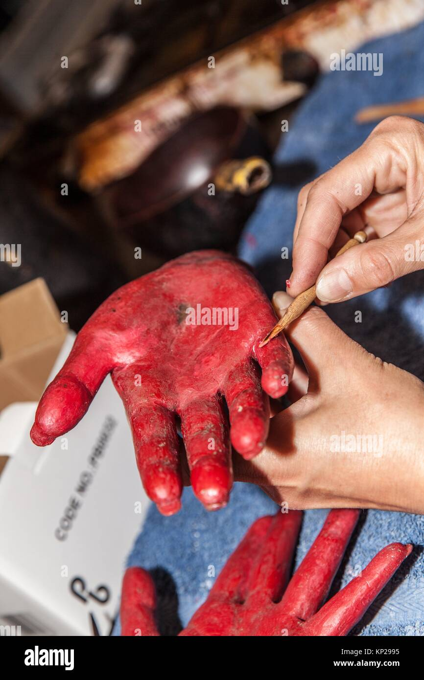 artisan in a workshop painting on a red sculpture - Stock Image