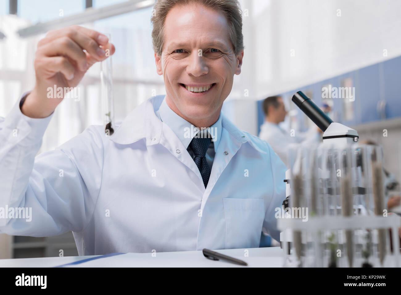 Smiling chemist holding test tube  - Stock Image