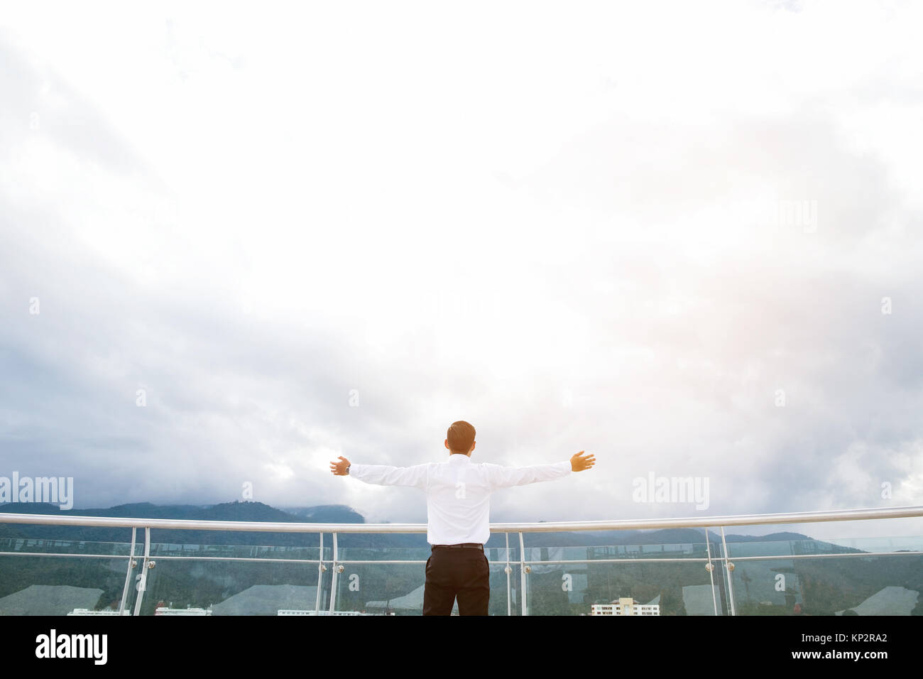 Businessman standing keeping arms raised on a roof and looking at city Success  concept - Stock Image