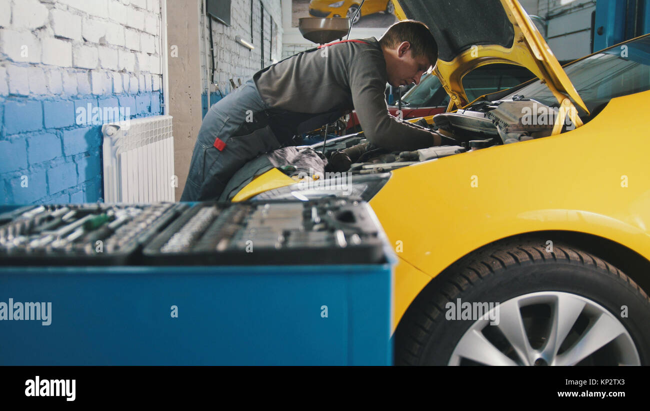 Mechanic in car service - repairing in engine compartment - Stock Image