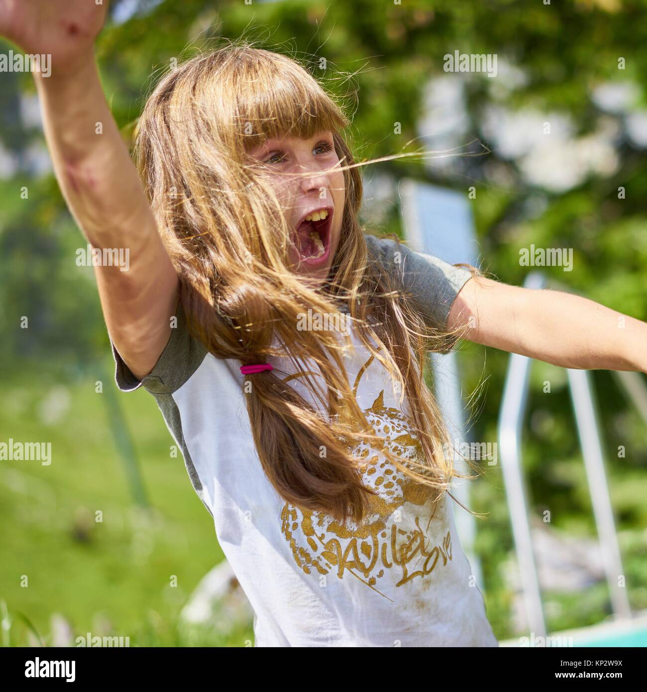Happy young female child going wild in nature and screeming out loud - Stock Image