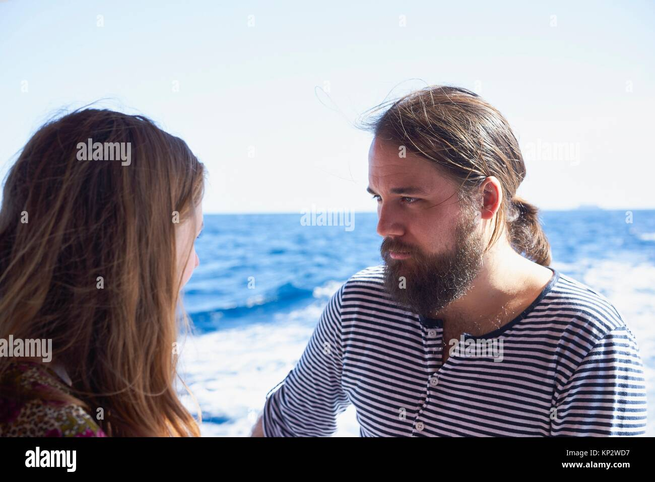 Romantic boyfriend with intense eye contact, next to blue ocean, Gozo, Malta - Stock Image