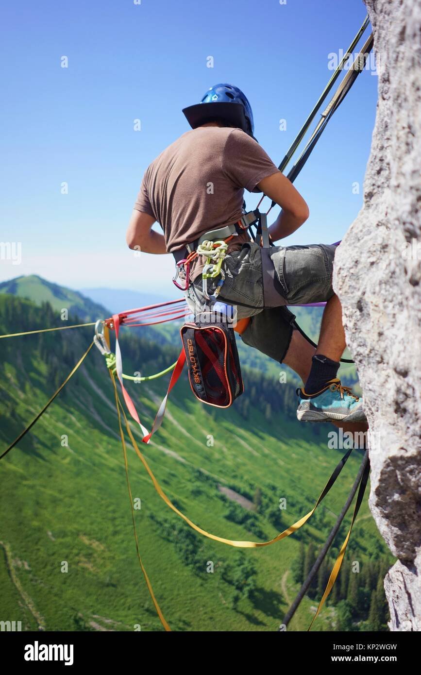 man at anchor point of highline slackline, checking safeguard, in Bavarian alps, near mountain Blankenstein, south - Stock Image