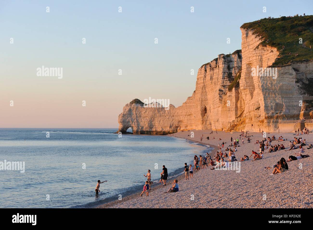 people enjoying sunset on the beach of Etretat, Seine-Maritime department, Normandie region, France, Europe. - Stock Image