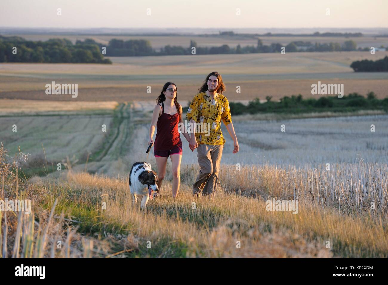couple of young people walking with a dog around Mittainville, Yvelines department, Ile-de-France region, France, - Stock Image
