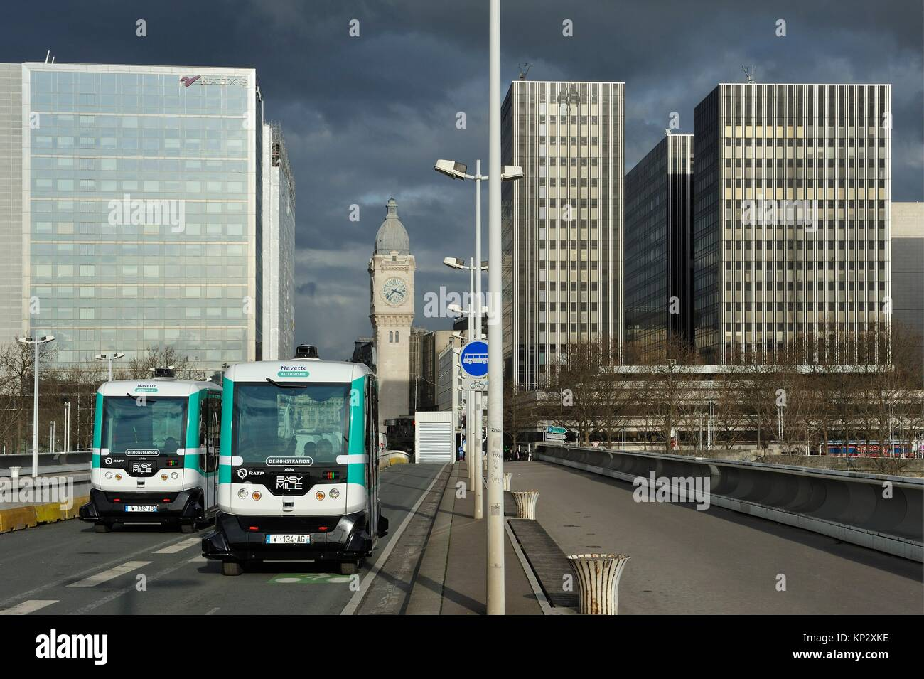 Autonomous shuttle in experiment by RATP on Charles-de-Gaulle Bridge with the Tower Clock of Gare de Lyon in the - Stock Image
