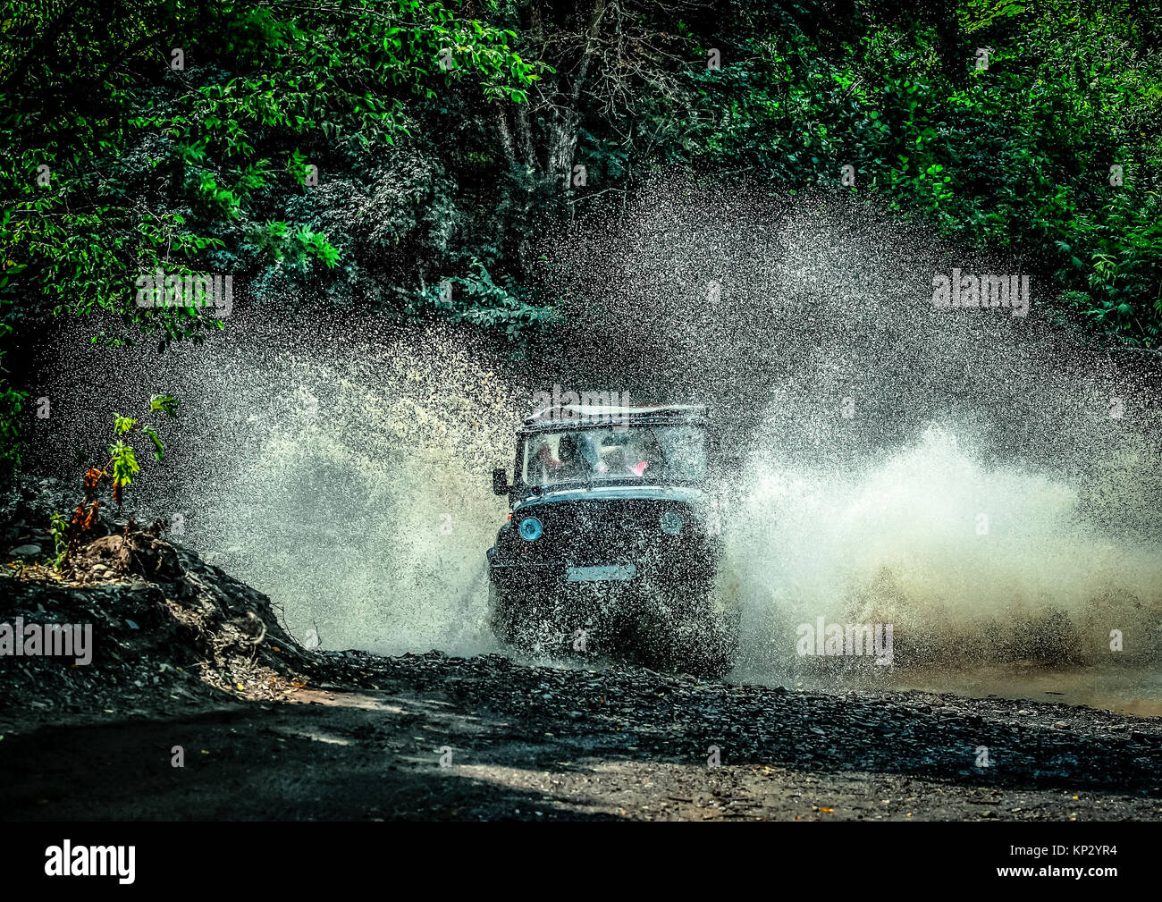 a trip on an off-road vehicle. off-road car at high speed crosses a mountain stream - Stock Image