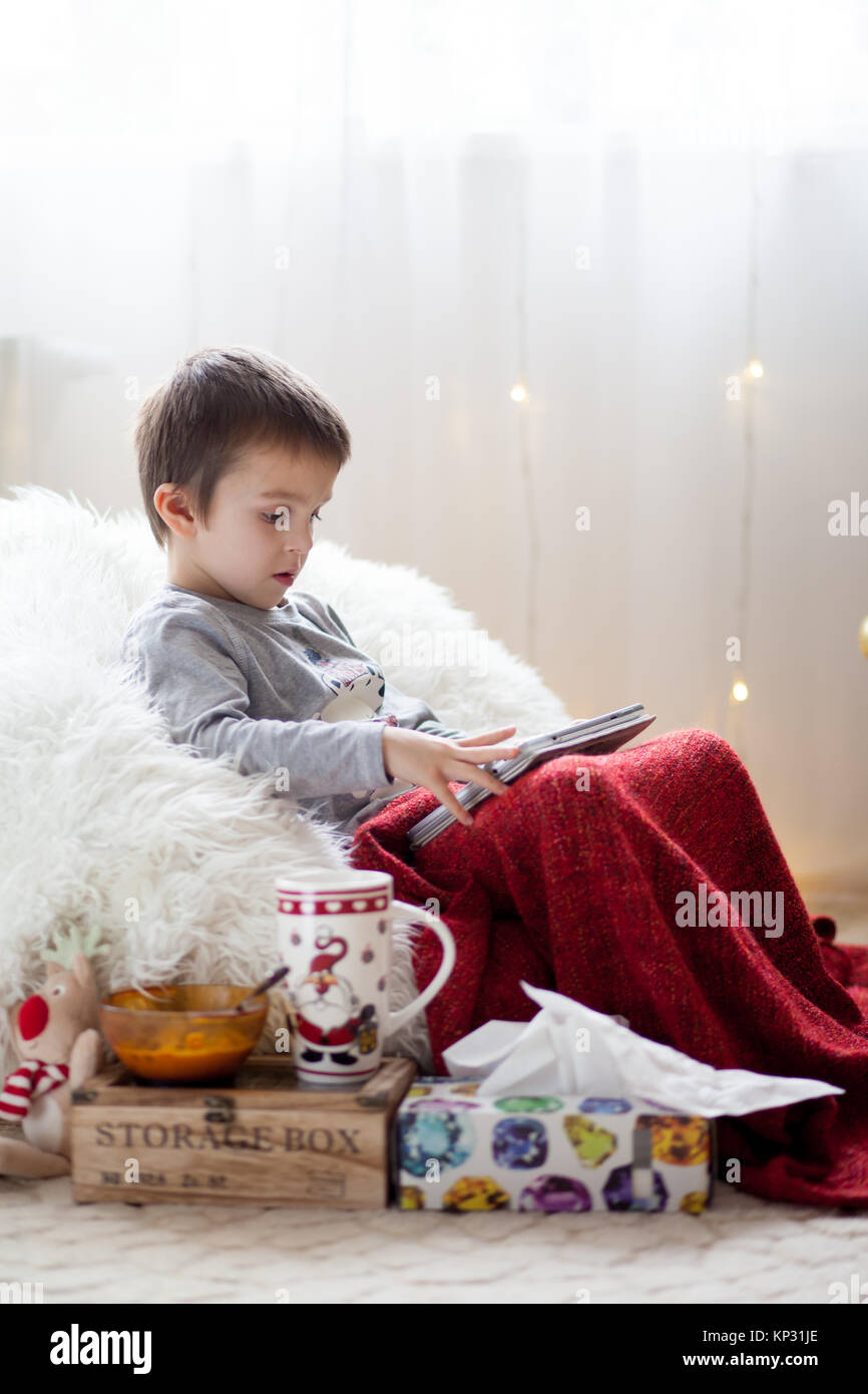 Cute little sick boy, sitting on bean bag, playing on tablet and drinking tea, lying down with a flu - Stock Image