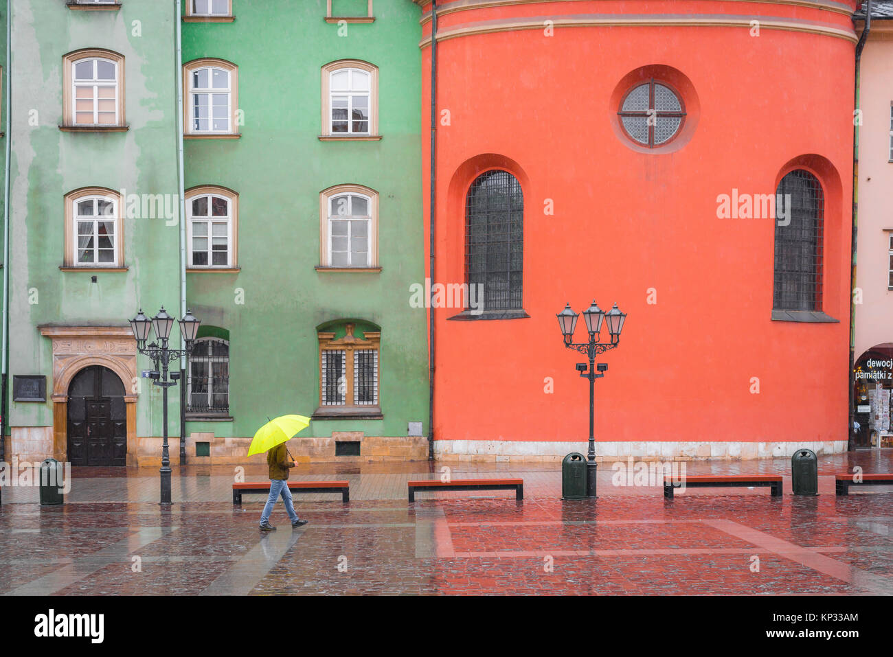 Man rain city, a man sheltering under a yellow umbrella walks past a row of colourful baroque buildings in Little - Stock Image