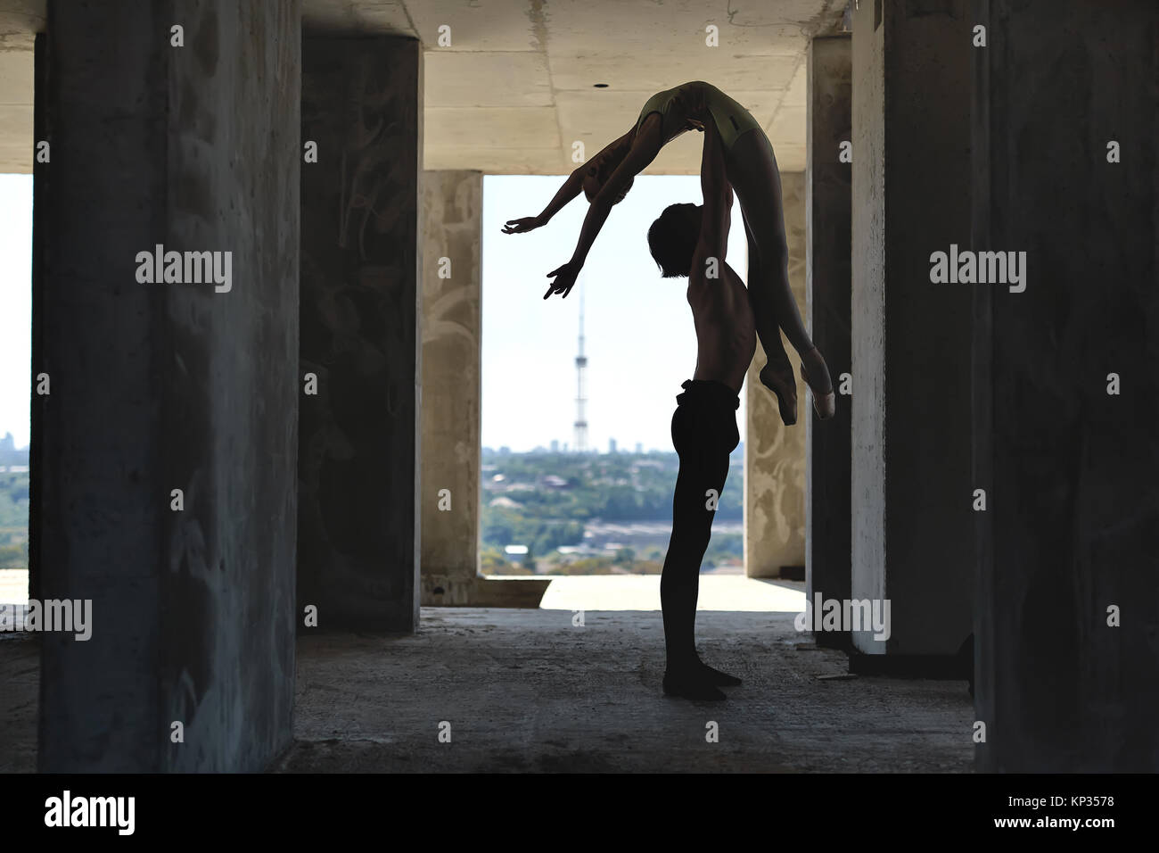 Silhouette of couple of ballet dancers who posing on the concrete floor of the unfinished building on the cityscape - Stock Image