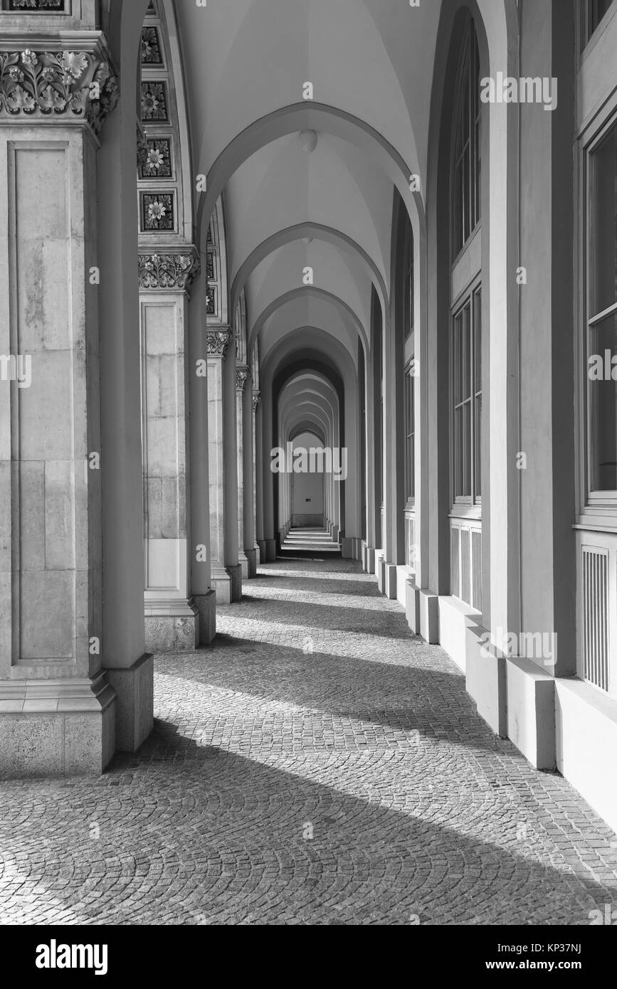 Portrait orientation of a row of arches archways outside a building creating a simple black and white pattern of - Stock Image