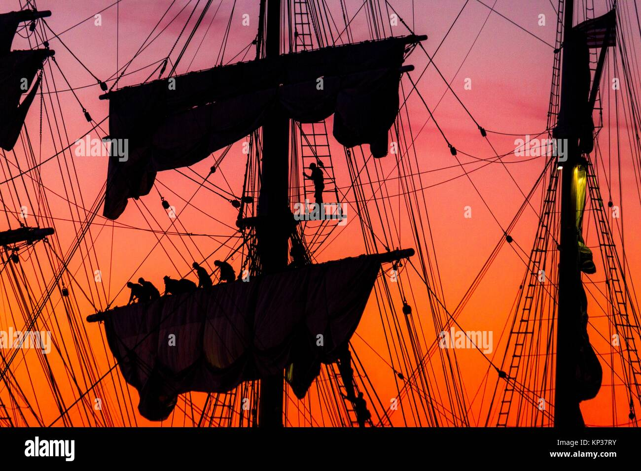 Sailors rolling up sails at sunset on the Star of India sailing ship in San Diego, CA - Stock Image