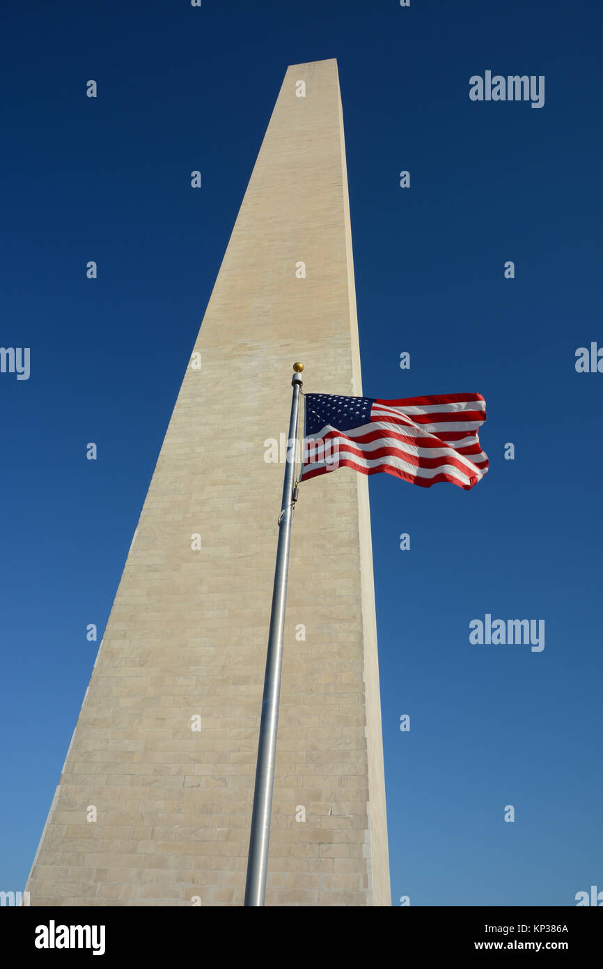 Washington Monument standing tall with an American flag flying on a flagpole in Washington DC, USA - Stock Image