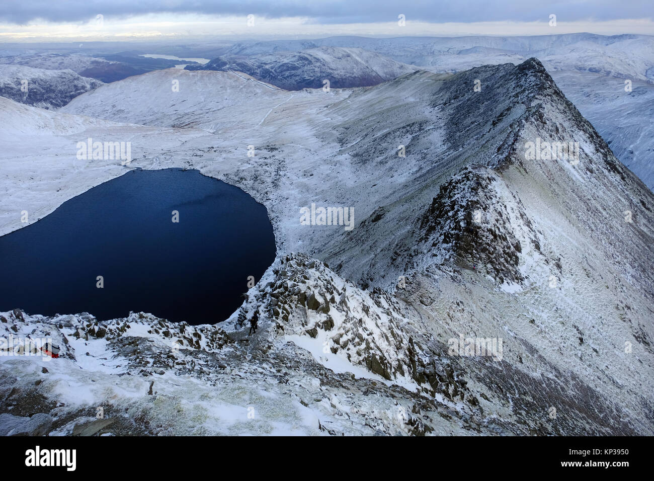 Striding Edge, a ridge leading onto the mountain of Helvellyn in The Lake District National Park, with a covering - Stock Image
