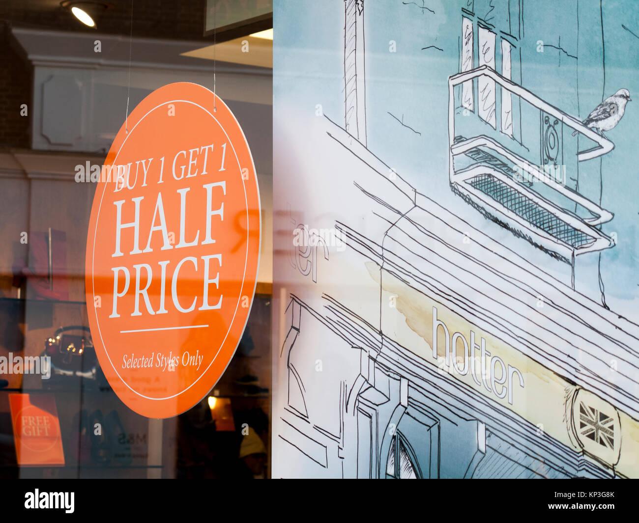 Hotter shoe shop window display advertising buy one get one half price - Stock Image