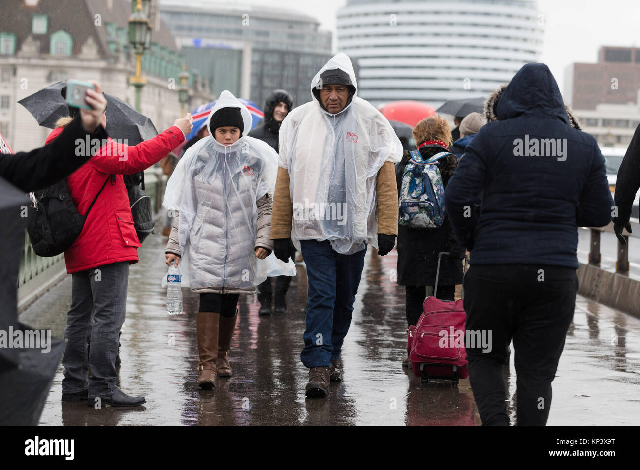 London, UK. 13th December 2017. Tourists wearing rain ponchos umbrellas walk in the rain on Westminster Bridge. - Stock Image