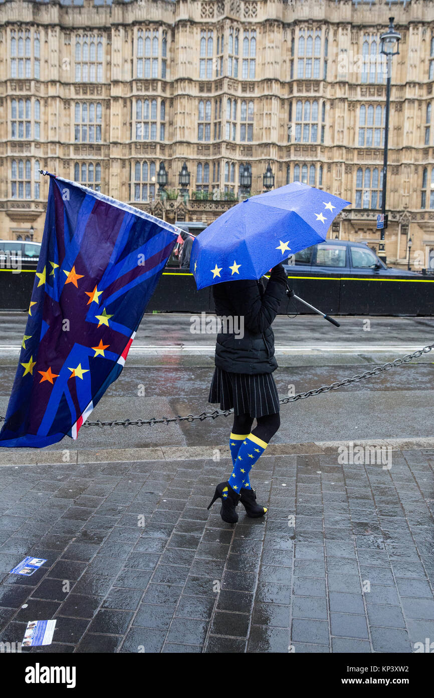 London, UK. 12th December, 2017. An anti-Brexit protester wearing EU socks and carrying an EU flag and a Union Jack - Stock Image