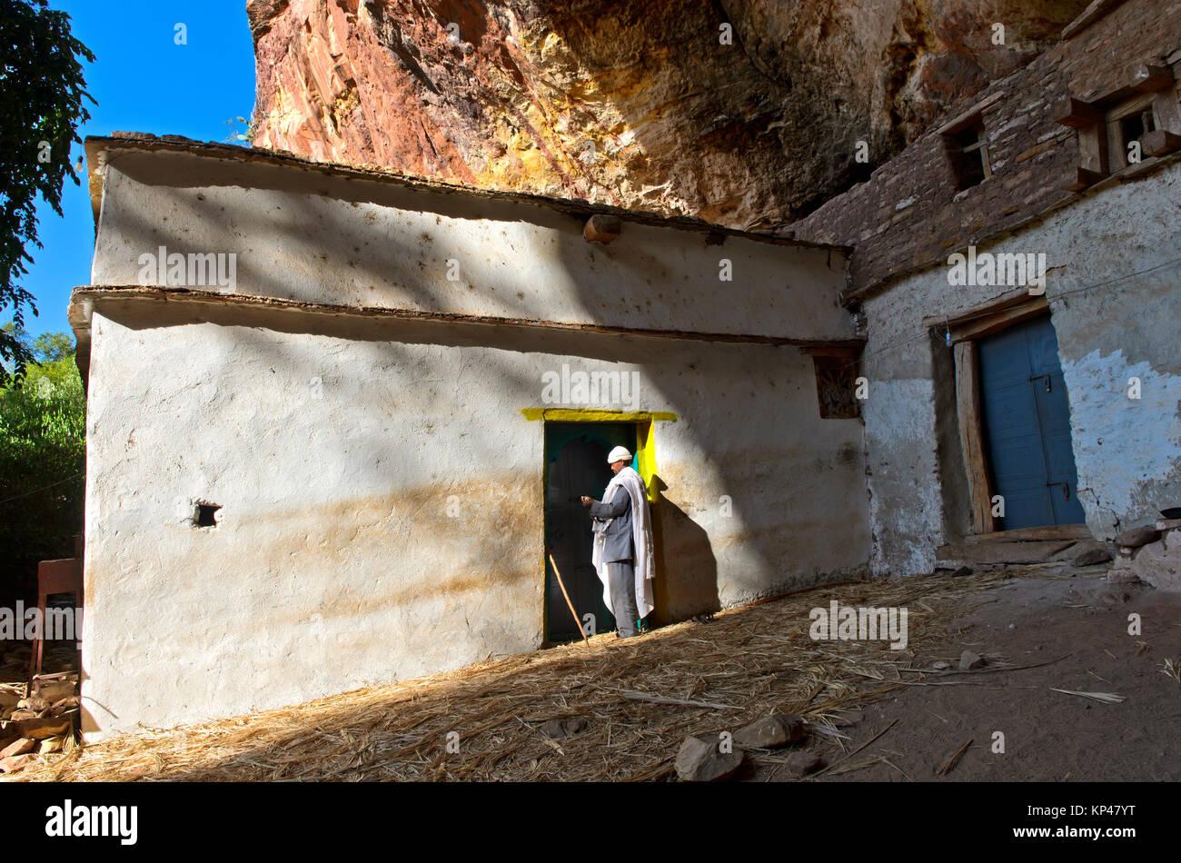 Priest at the entrance to the rock church Maryam Papaseyti, Gheralta, Tigray, Ethiopia - Stock Image