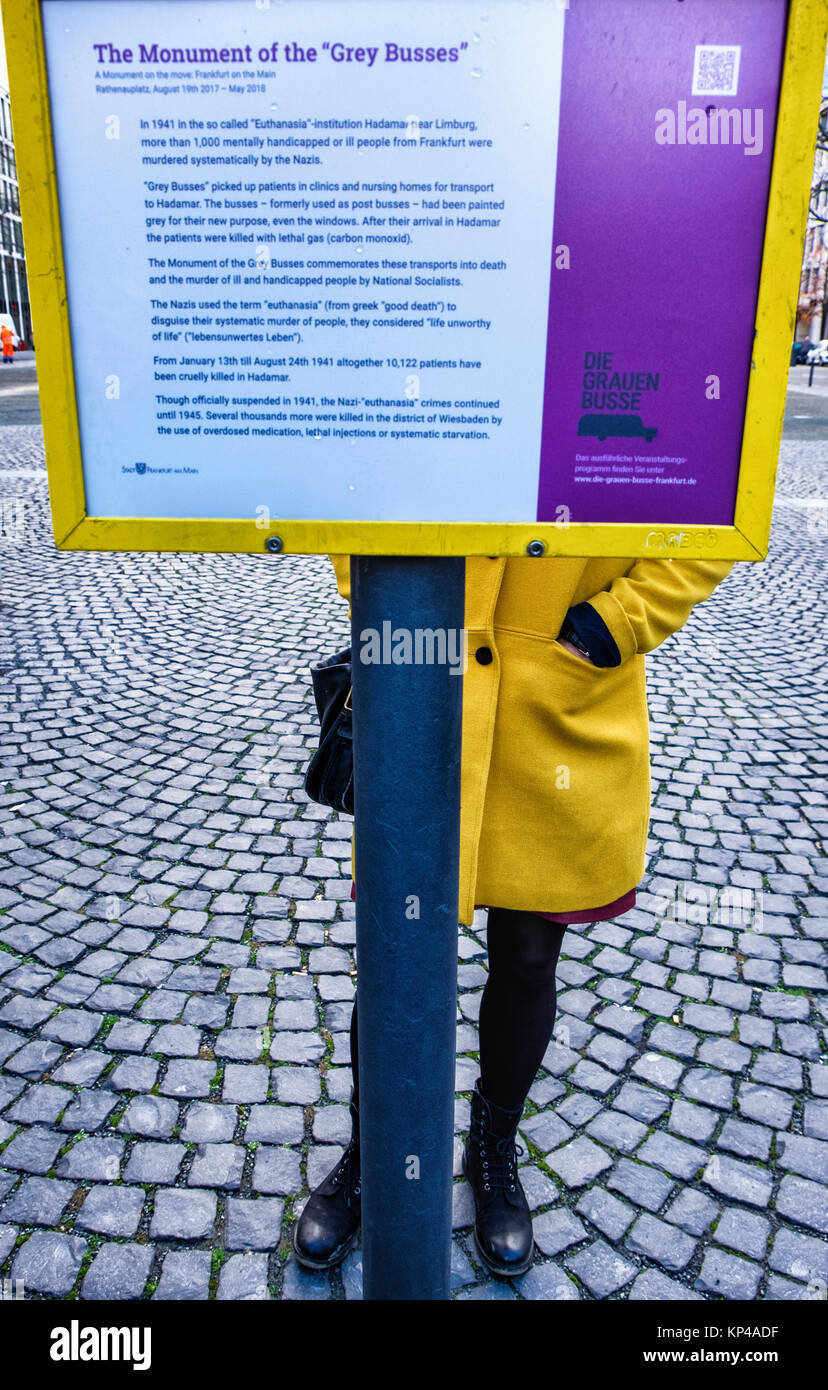 Frankfurt,Germany.Young woman in yellow coat reads Grey Buses Monument information board. Memorial commemorates Stock Photo