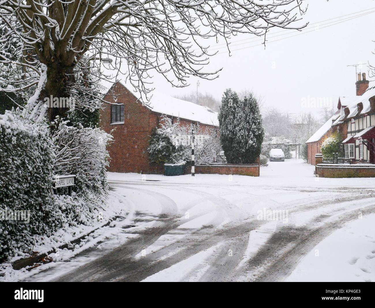 A wintry village scene: tracks in the snow on a quiet lane in England - Stock Image