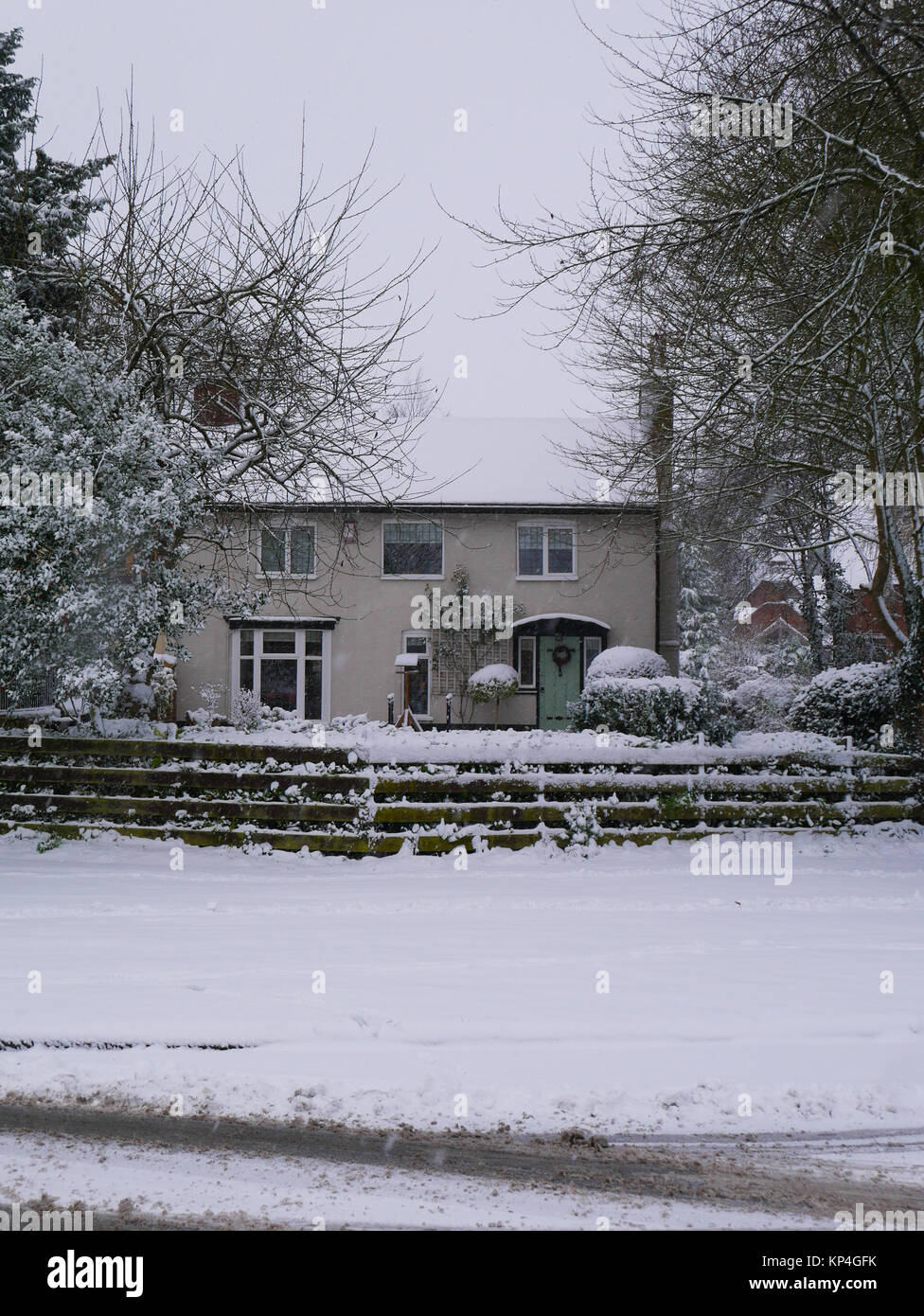 A pretty English cottage in the snow - Stock Image