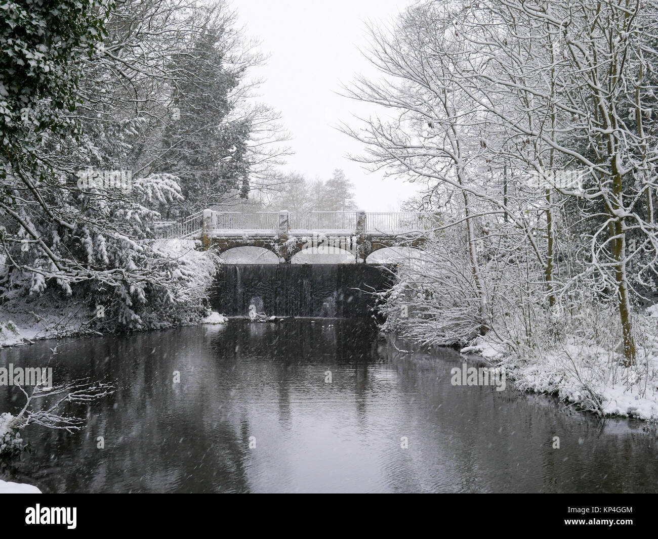 Wintry scene: Bridge over the River Dove, on a snowy day in the village of Rolleston on Dove, Staffordshire - Stock Image