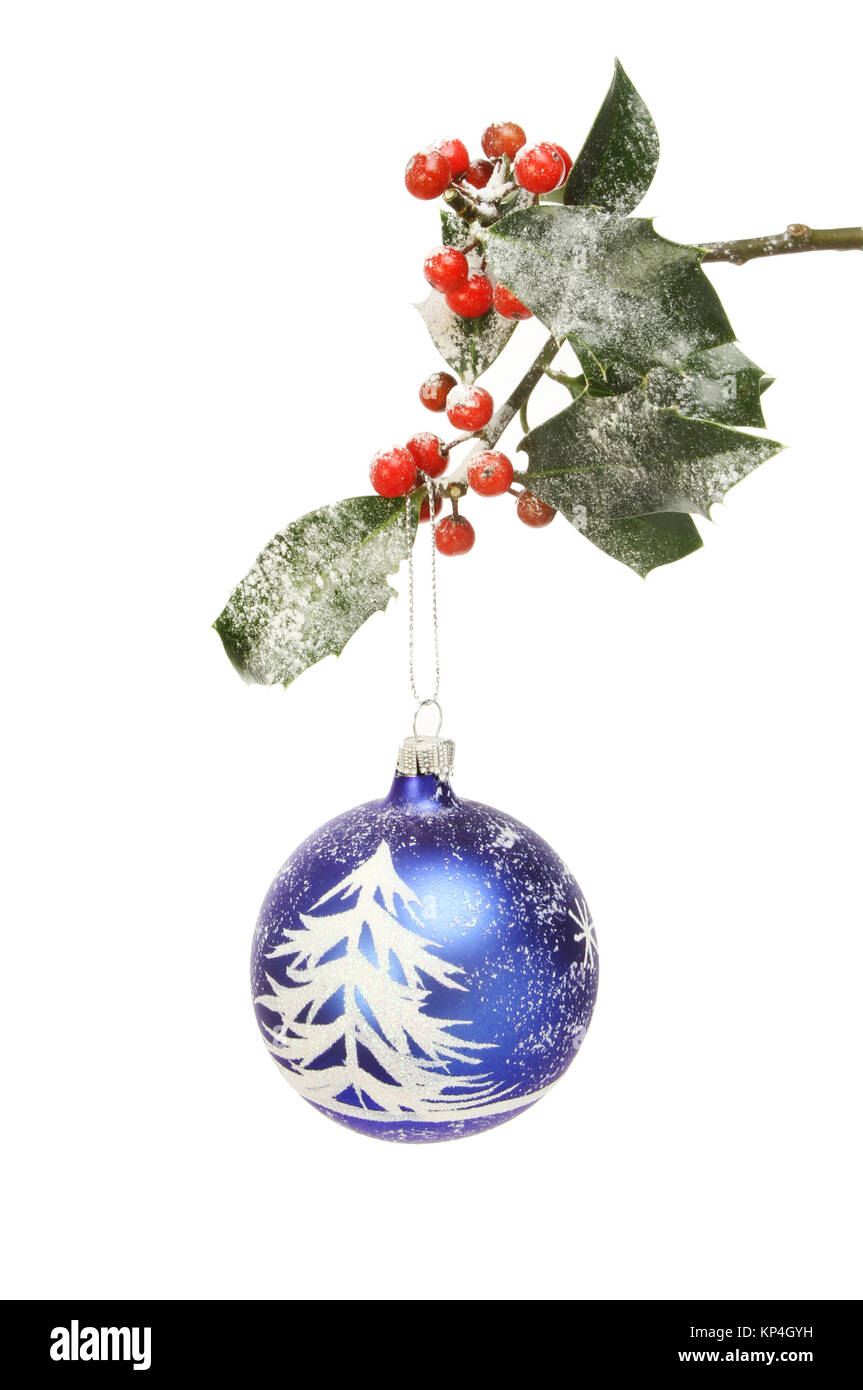 Snow scene Christmas bauble hanging from a snow dusted holly branch - Stock Image