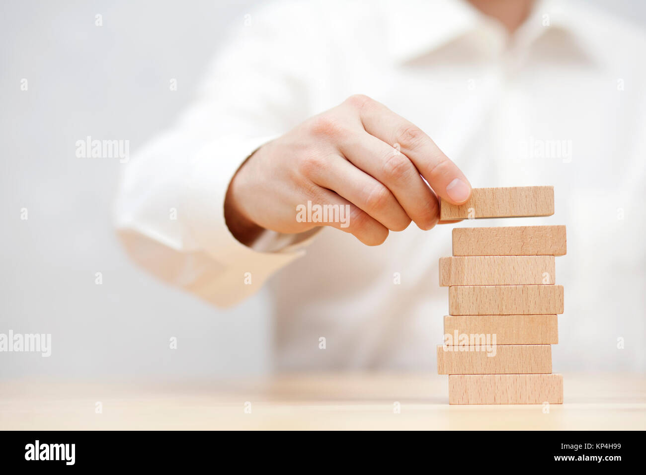 Man's hand stacking wooden blocks. Business development concept. - Stock Image