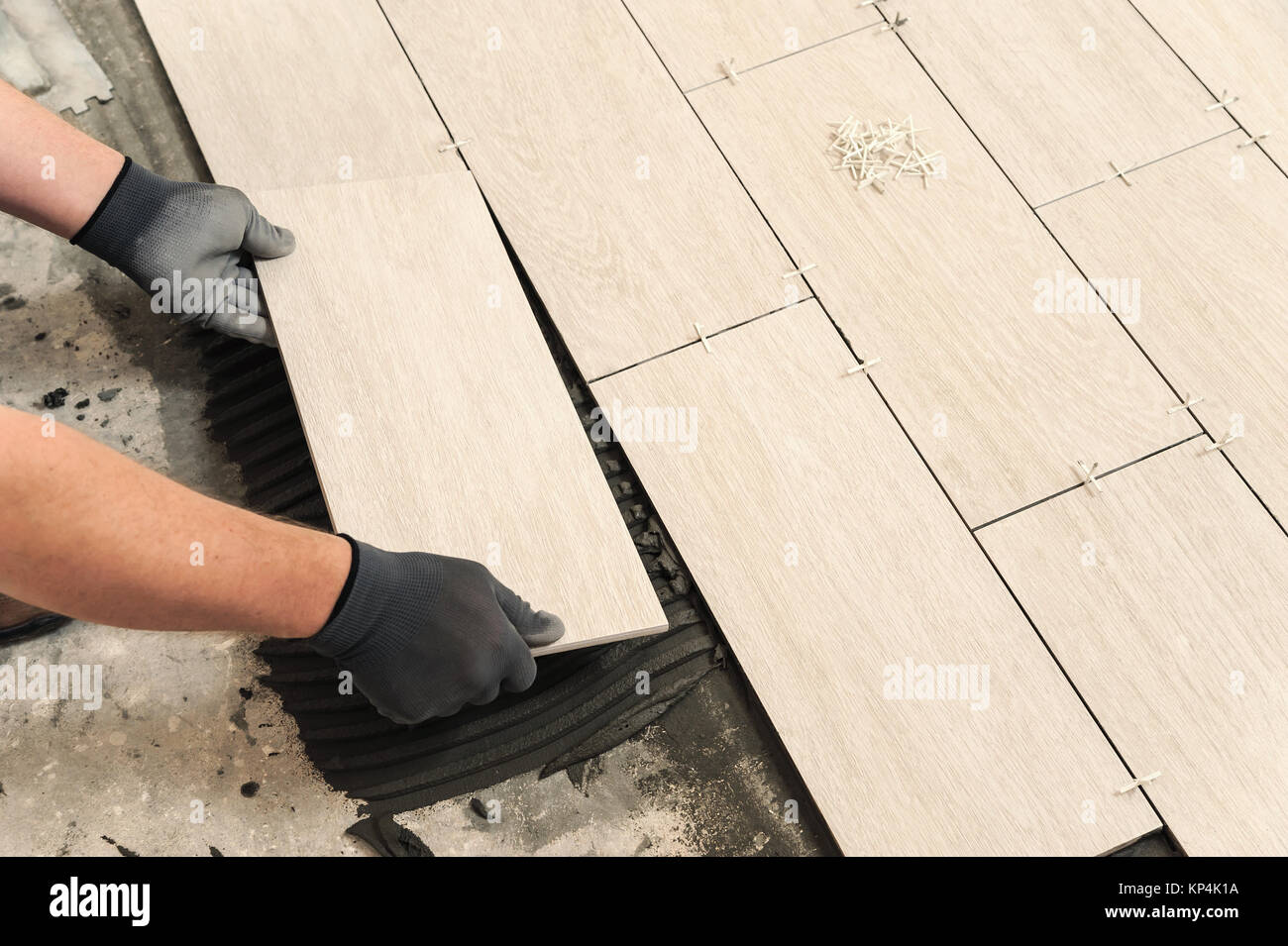 Laying Ceramic Tiles. Man placing ceramic floor tile in position ...