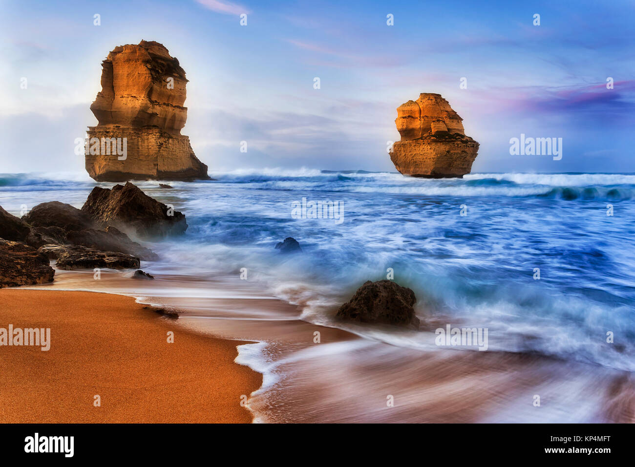 two apostless off Gibson Steps beach at sunrise in surfing waves breaking limestone cliffs and rocks - part of famous Stock Photo